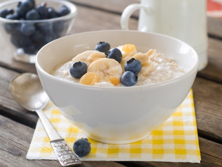 Bowl of oatmeal porridge with bananas and blueberry, selective focus Stock Photo