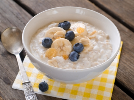 Bowl of oatmeal porridge with bananas and blueberry, selective focus Stockfoto