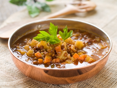 Brown lentil soup in bowl with vegetable, selective focus