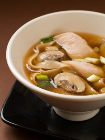 Asian noodle soup with chicken and mushrooms, selective focus photo
