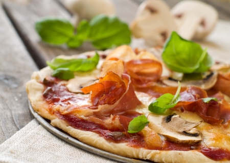 Pizza with prosciutto, mushroom and basil, selective focus Stock Photo