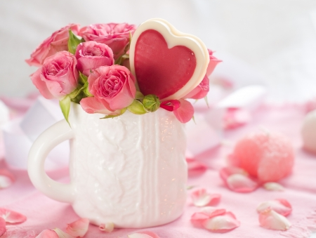 Pink roses in white cup with lollipop for celebration photo