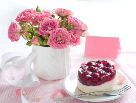 Strawberry cake and pink roses in white cup for celebration photo