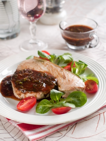 Grilled tuna steak with sauce and salad, selective focus photo