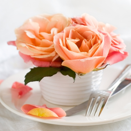 Place setting with rose, fork andknife, selective focus photo