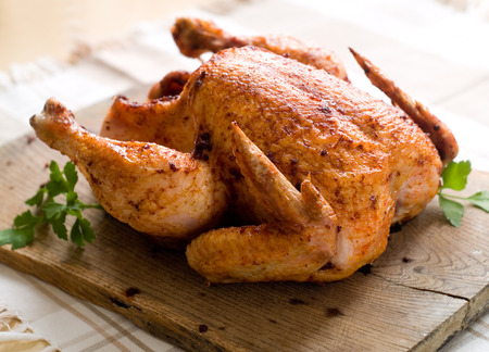 roasted chicken: Whole roasted chicken on wooden board
