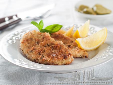 chicken: Pollo o schnitzel de cerdo con gajos de lim�n, el enfoque selectivo Foto de archivo