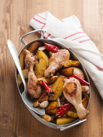 ovenbaked: Oven-baked chicken legs with potatoes, selective focus