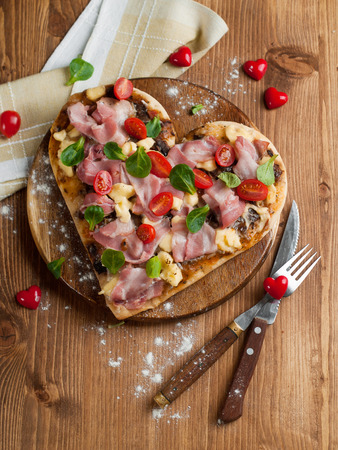 bacon love: Heart shaped pizza with bacon and vegetables, selective focus