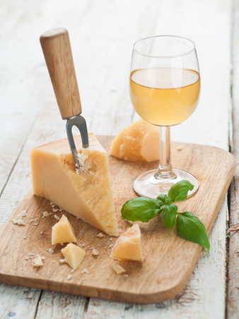 Parmesan cheese on cutting board with wine,  basil and knife, selective focus