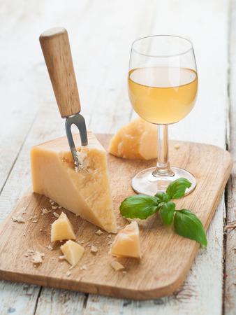 queso: Queso parmesano en la tabla de cortar con el vino, la albahaca y el cuchillo, el enfoque selectivo