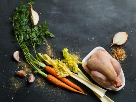 stocks: Fresh chicken and vegetables on dark vintage background, selective focus. Healthy food, diet or cooking concept Stock Photo