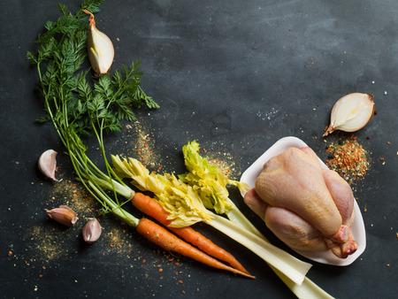 chicken: Pollo y hortalizas frescas en el fondo oscuro de la vendimia, foco selectivo. La comida sana, la dieta o el concepto de cocina Foto de archivo