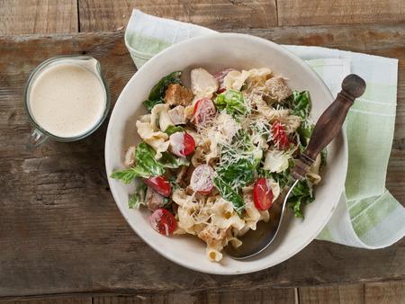ensalada cesar: Ensalada de pasta con pollo, tomate, queso y salsa, enfoque selectivo
