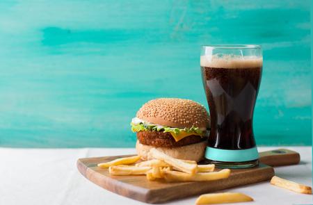 alimentos y bebidas: Cheeseburger con cola y papas, enfoque selectivo