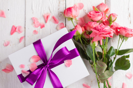 red gift box: Roses and gift on wooden board, Valentines Day background, selective focus Stock Photo