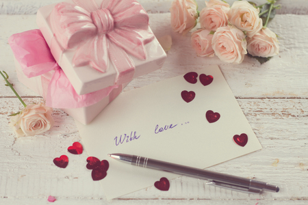 Gift, hearts, flower and greeting card on wooden background in vintage style, selective focus
