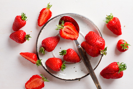 sweet and savoury: Fresh strawberries on plate on wooden board, selective focus