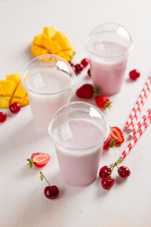 berry: Berry  and ice cream milkshake (smoothie) with fresh berry  in plastic glass, selective focus Stock Photo