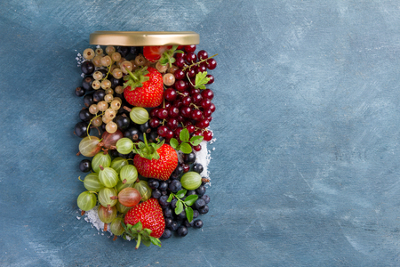 Different fresh berries like a jar for summer preserves cooking concept, selective focus