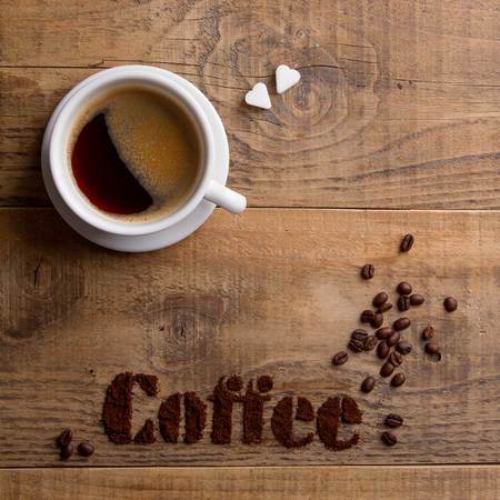 Coffee composition with cup and coffee beans on wooden background, selective focus