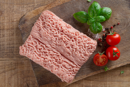 Minced chicken or turkey meat on wooden board with basil and spices, selective focus