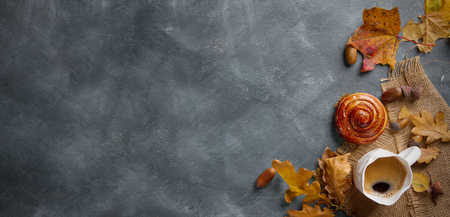 Hot coffee in mug with cinnamon bun and autumn leaf on a vintage table surface, selective focus