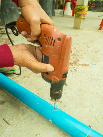 making hole: hands hold electric drill Stock Photo