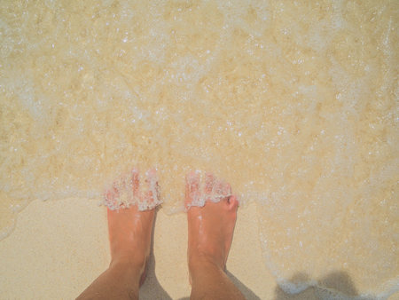 come in: a wave comes in, as I stand and wait. copy space. top down view, my feet waiting for the water to come in, sand, beach