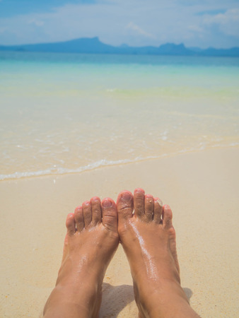 painted toenails: a wave comes in, as I stand and wait. copy space. top down view, my feet waiting for the water to come in, sand, beach