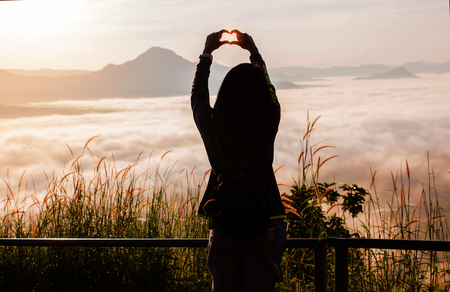 Young Woman standing alone outdoor with wild forest mountains on background Travel Lifestyle and love concept rear view,Woman spreading hands with joy and inspiration in mountains.