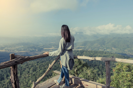 Young Woman standing alone outdoor with wild forest mountains on background Travel Lifestyle and survival concept rear view, Woman spreading hands with joy and inspiration in mountains.
