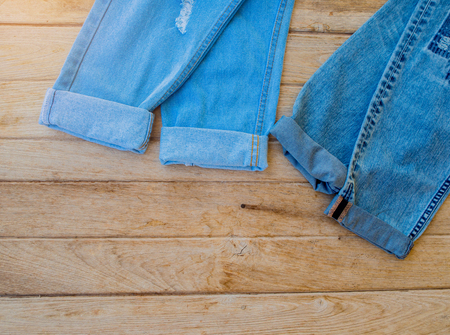 worn: Blue jeans folded on wooden background, Ripped Destroyed Torn Blue jeans background. Stock Photo