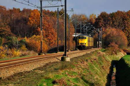 Railway and train coming out of the autumn yellow forests