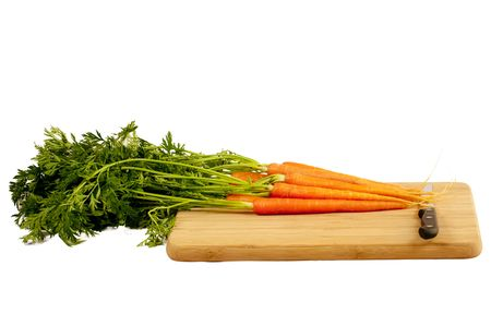 carrots with knife on a wooden cutting board