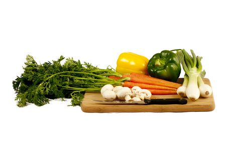 several vegetables on a wooden cutting board