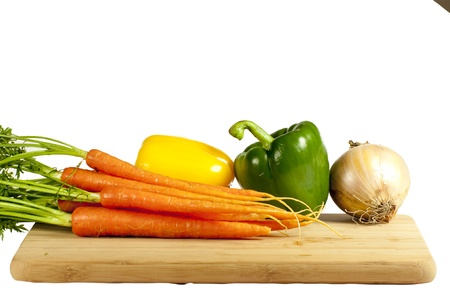 Several vegetables on a wooden cutting board photo