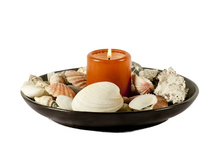 burning candle with shells isolated on a white background