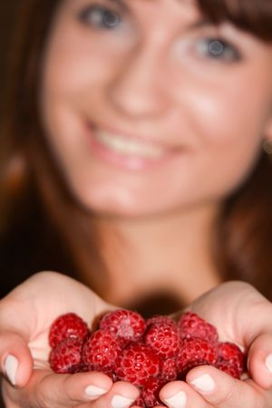 giggle: This is a portrait of a girl holding raspberries in her hands. Stock Photo