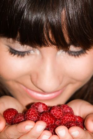 This is a portrait of a girl holding raspberries in her hands. Stock Photo
