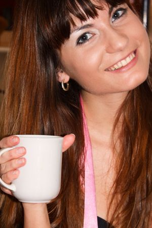 This is a portrait of a smiling girl with a mug in her hand.