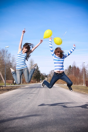Two girls are jumping on the road. They seem happy and they have baloons in their hands. Stock Photo