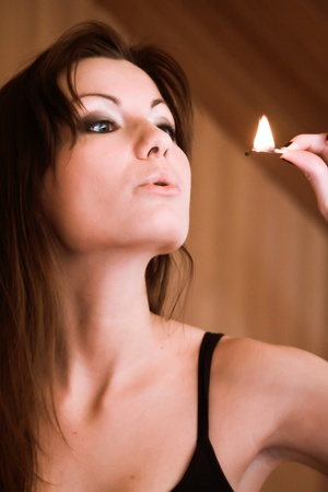 This is a portrait of a young girl, She is holding a match in her hand. Stock Photo