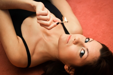 This is a portrait of a girl. She is lying on the floor and holding a burning match in her arm. photo