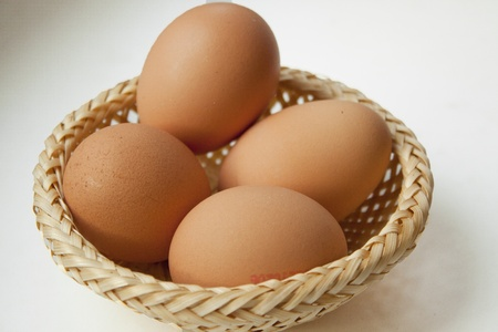 Basket with several eggs is standing on the table.