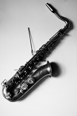 a black and white picture of a saxophone hanging on the wall