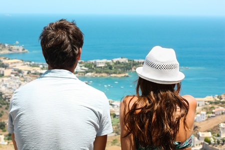 Picture of a young couple sitting side by side and looking at the blue sea.