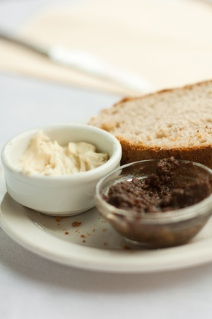 Two little pots with sauces and a slice of bread on the plate.