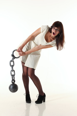 Photo of a girl posing and pretending to lift heavy weight. Stock Photo