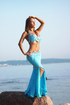 Beautiful lady in eastern costume on the sea shore photo